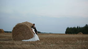 Love couple goes on cleaner wheat field on the field are seen haystacks stock video footage