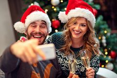 Love couple having fun and take pictures of Christmas on mobile. Phone at home royalty free stock image
