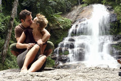 Love couple kissing. A love couple kissing each other before a waterfall Royalty Free Stock Photos