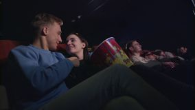 Love couple kissing in cinema. Romantic couple embracing in movie theatre