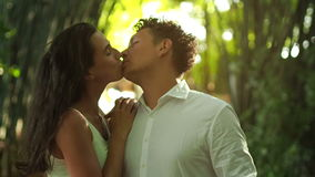 Love couple kissing. Close up of romantic couple kiss in green bamboo forest stock video footage