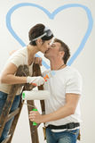 Love couple kissing in new home. Young couple painting new home. Standing on ladder, kissing. Isolated on white background Stock Image