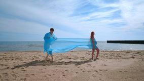 Love couple kissing rolled in fabric at beach. Romantic relationship concept stock video