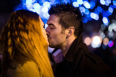 Love - couple kissing in street at night stock photography
