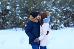 Love couple kissing in winter pine forest. Happy vacations together royalty free stock image