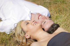 Love couple laughing lying on grass in summer day Royalty Free Stock Image