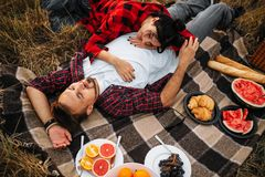 Love couple lies on plaid, picnic in summer field royalty free stock photography