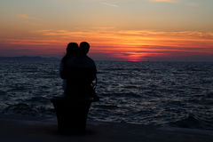Love Couple. A loving couple sitting together to watch the world`s most beautiful sunset at Zadar, Croatia stock photography