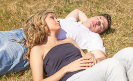 Love couple lying on the grass in a summer day Royalty Free Stock Photo