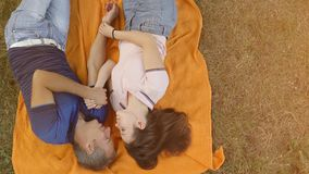 Love couple lying on orange plaid, top view Royalty Free Stock Photography
