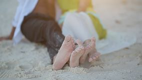 Love couple lying on the sand and their bare feet. Love game of feet. The ray of the sun at sunset slips in the frame. Love couple lying on the sand and their stock video footage