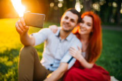 Love couple makes selfie in summer park on sunset. Love couple makes selfie on phone camera in summer park on sunset. Romantic date of attractive women and young Stock Photo