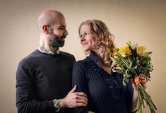 In love couple. Man gives flowers to wife as a gift stock photography