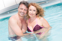In love couple, middle aged relaxing by pool Stock Image