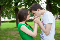Love couple out in the park. boy kisses girl's hands Royalty Free Stock Image