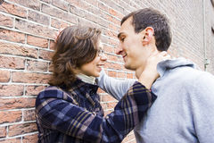 Love couple outdoor looking happy against wall backg. Portrait of love couple outdoor looking happy against wall background Royalty Free Stock Images