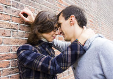 Love couple outdoor looking happy against wall backg. Portrait of love couple outdoor looking happy against wall background Stock Image