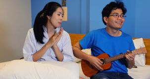 Love couple playing Ukulele and guitar in bed stock images