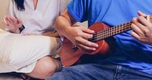 Love couple playing Ukulele and guitar in bed stock photography