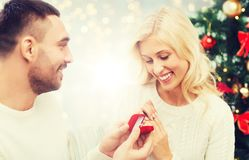 Man giving woman engagement ring for christmas. Love, couple, proposal, holidays and people concept - happy men giving diamond engagement ring in little red box royalty free stock photography