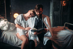 Love couple reading a book in hospital room Stock Photo