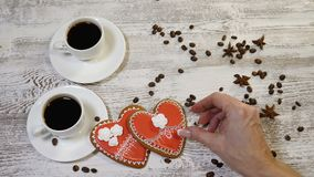 Love couple relations. St. Valentine concept. Top view of two cups of coffee and heart shaped ginger biscuit on wooden. Background with coffee beans around stock footage