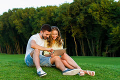 In love couple relaxing in the park. Guy and girl play games on the tablet. Communication on the Internet in the park. A date of lovers on the nature Royalty Free Stock Photography