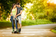 Love couple ride rollerblades in the park Stock Photos