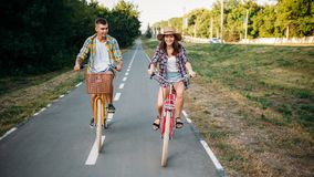 Love couple riding on retro bikes in summer park Royalty Free Stock Photo