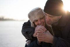 Man comforting his woman in severe cold Stock Images