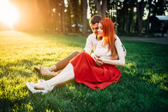 Love couple sits on grass in park, romantic date Royalty Free Stock Photo