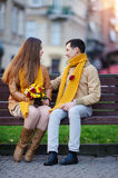 Love couple sitting on a bench with a bouquet of flowers Royalty Free Stock Image