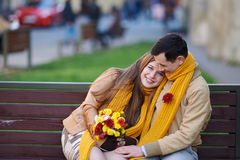 Love couple sitting on a bench with a bouquet of flowers Royalty Free Stock Photos