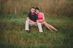 Love couple sitting on the grass Stock Photo