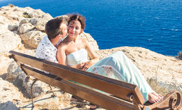 Love couple sitting outdoors on a bench looking the sea and sky in background Royalty Free Stock Photo