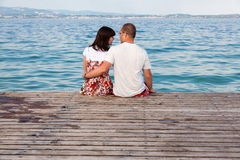 Love couple sitting on a pier overlooking the sea Royalty Free Stock Images