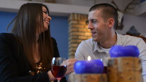 Love couple sitting at a table and drink wine stock video
