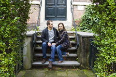 Love couple sitting on traditional Dutch porch looking happy. Portrait of love couple sitting on traditional Dutch porch looking happy Stock Image