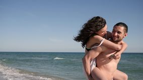 Love couple on Summer vacation, happy girl jumping on guy`s back, wind develops hair, tropics, along ocean coast,. On background beautiful beach, travel, slow stock video