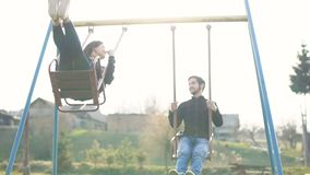 Happy young guy and girl ride on a swing. Outdor. Sunset stock footage