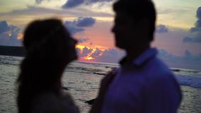 Love couple at sunset in a sea. Embracing silhouette stock video
