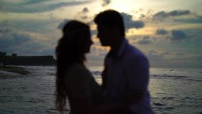 Love couple at sunset in a sea. Embracing silhouette stock footage