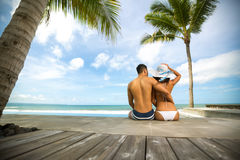 Love couple in tropical resort. Sitting on sea cost and looking at sea, back view Royalty Free Stock Photos