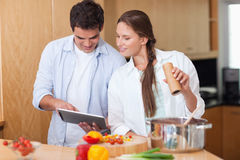 In love couple using a tablet computer to cook Royalty Free Stock Photography