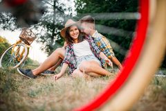 Love couple with vintage bikes sitting on grass Royalty Free Stock Image