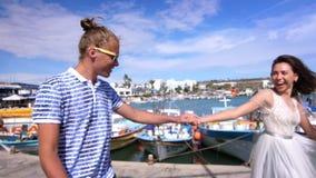 Honeymoon travel. Love couple walking on embankment with moored ships stock video
