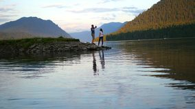 Love couple walking on river at sunset stock footage