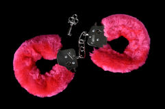 Love Cuffs. Pink furry handcuffs with a key closeup isolated on black background Royalty Free Stock Image