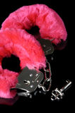 Love Cuffs. Pink fluffy handcuffs with a key closeup isolated on black background Royalty Free Stock Photography