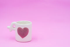 Love cup on pink background, Pink heart on cup. Royalty Free Stock Images